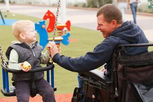 Bild vergrößern: Disabled Father play with his little son on the playground.